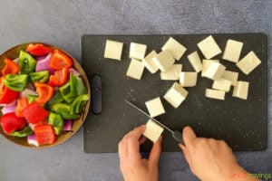 two hands cubing paneer on cutting board with chopped peppers on side