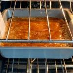 cinnamon-sugar topped apple cake in baking pan in oven