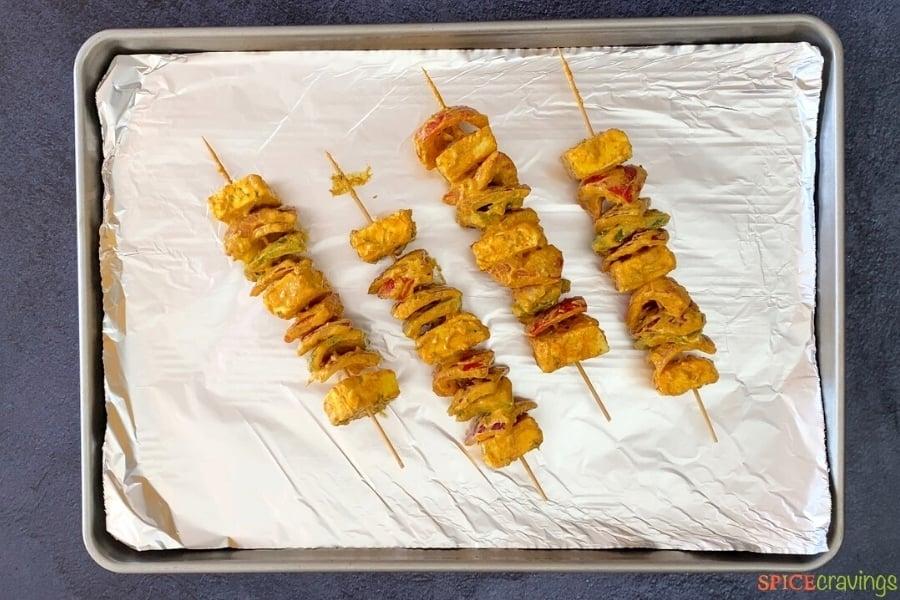 four prepared paneer tikka skewers on foil-lined baking sheet