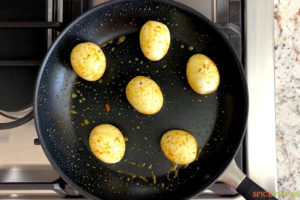 spiced hard boiled eggs sauteeing in skillet