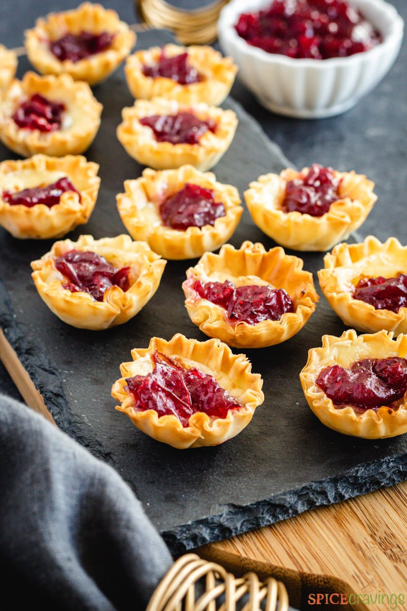 Cranberry cheese bites on a tray next to a bowl of cranberry sauce