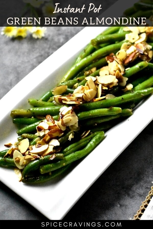 A white plate with sautéd green beans with almonds