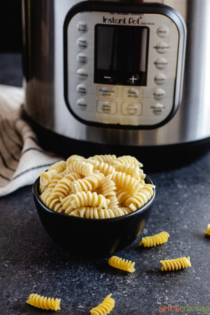 A bowl of rotini pasta next to an Instant Pot