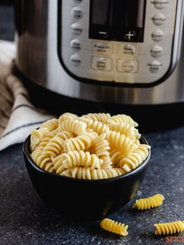 A bowl of cooked rotini pasta next to an instant pot