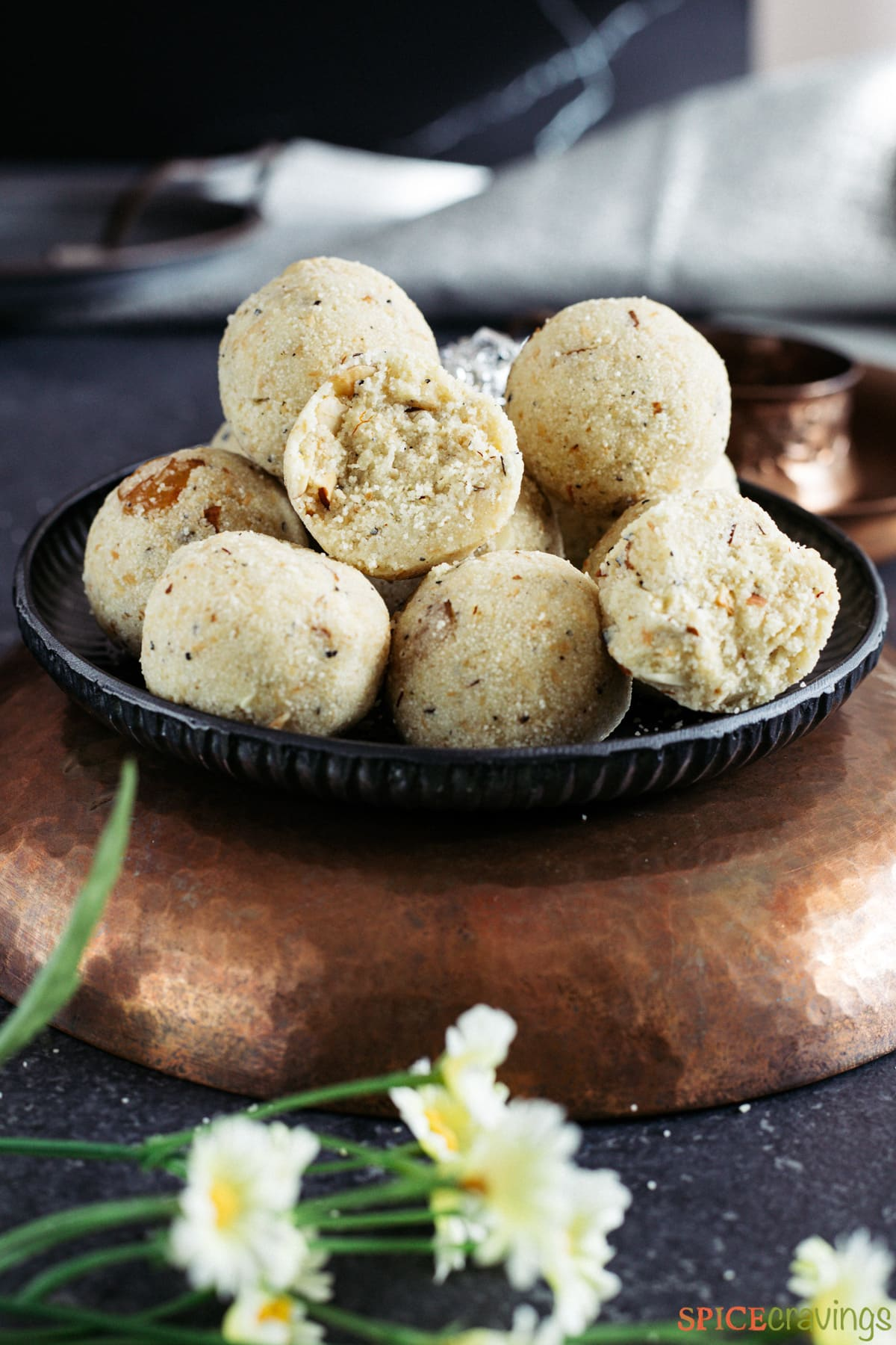 Rava laddu split in half, placed with other ladoos on metal plate