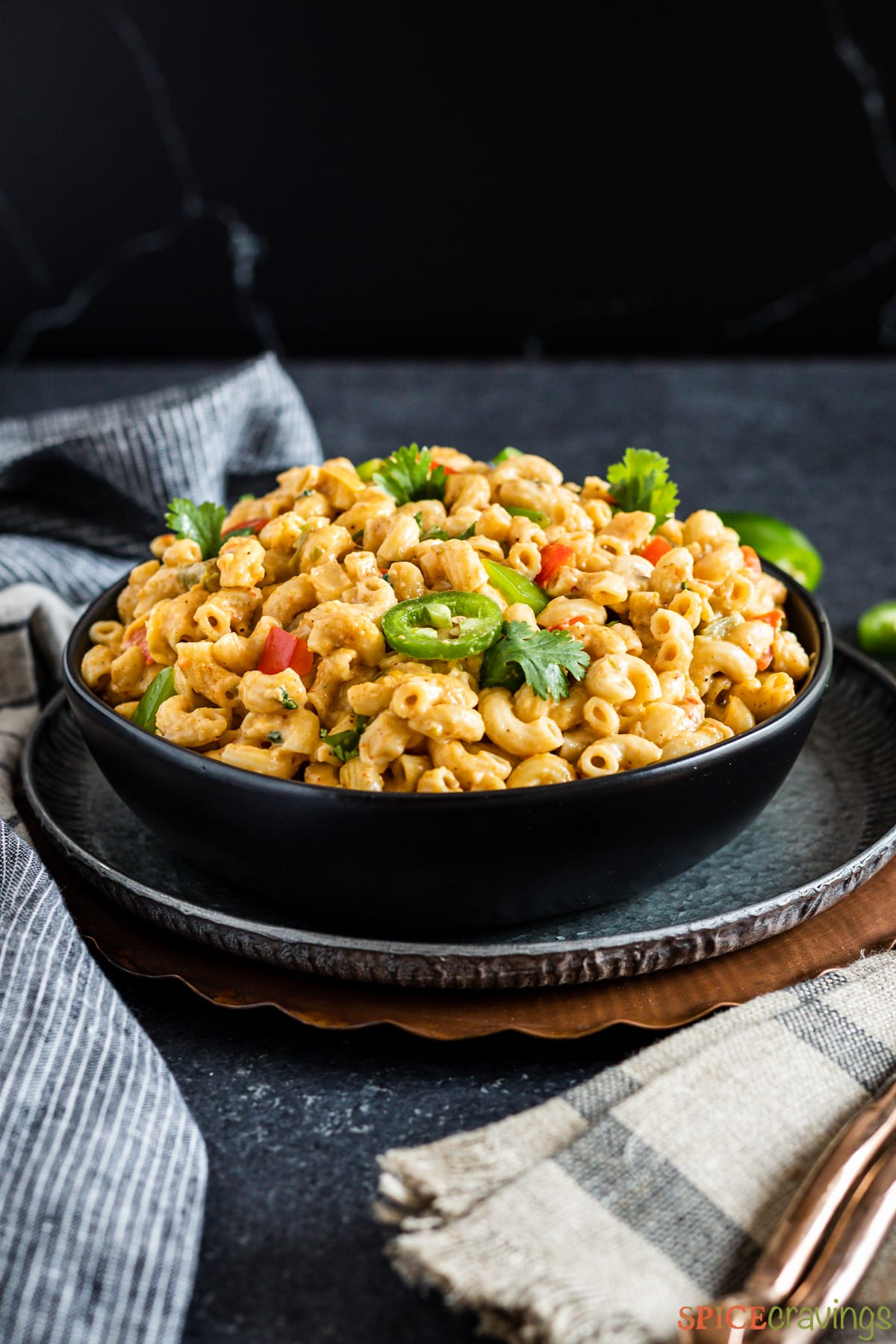 A bowl of spicy macaroni and cheese topped with veggies