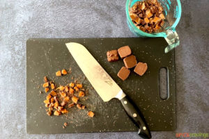Chopped caramel pieces next to a chefs knife