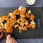 Hands cutting pieces of croissants on a cutting board
