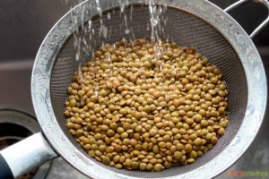 Rinsing lentils in a strainer over the sink