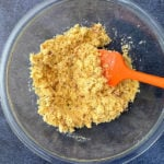 Wet semolina mix in a bowl with orange spatula