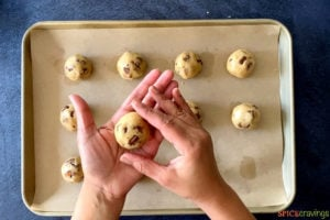 Hand holding a rolled cookie dough ball