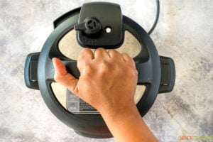 A hand placing a lid on an Instant Pot