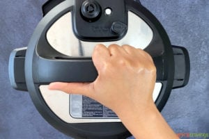 A hand putting the lid on an Instant Pot