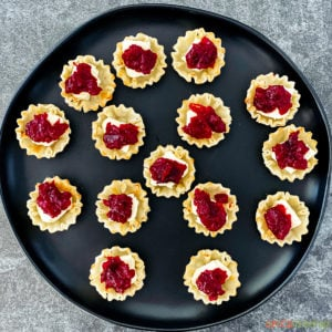 Uncooked phyllo cups with brie and cranberry sauce inside