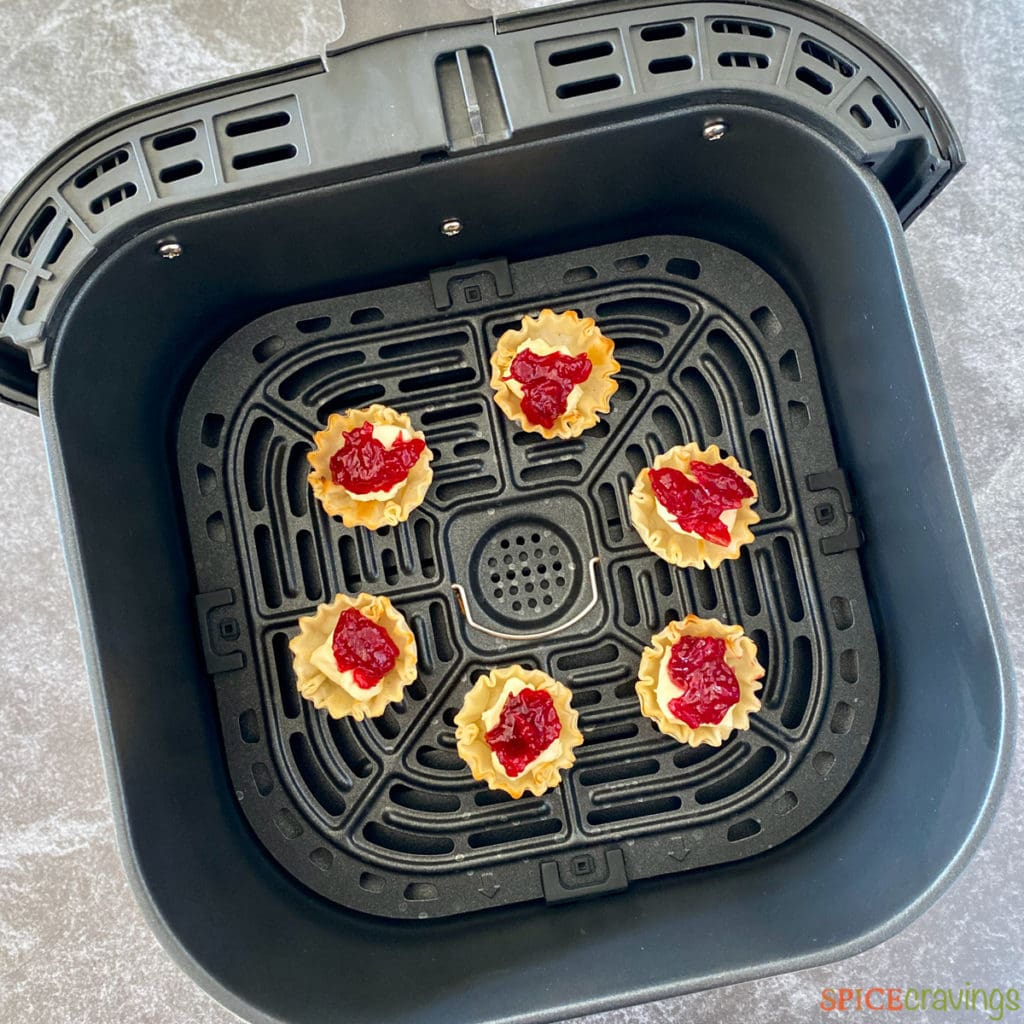 Cranberry bites with brie inside an air fryer basket