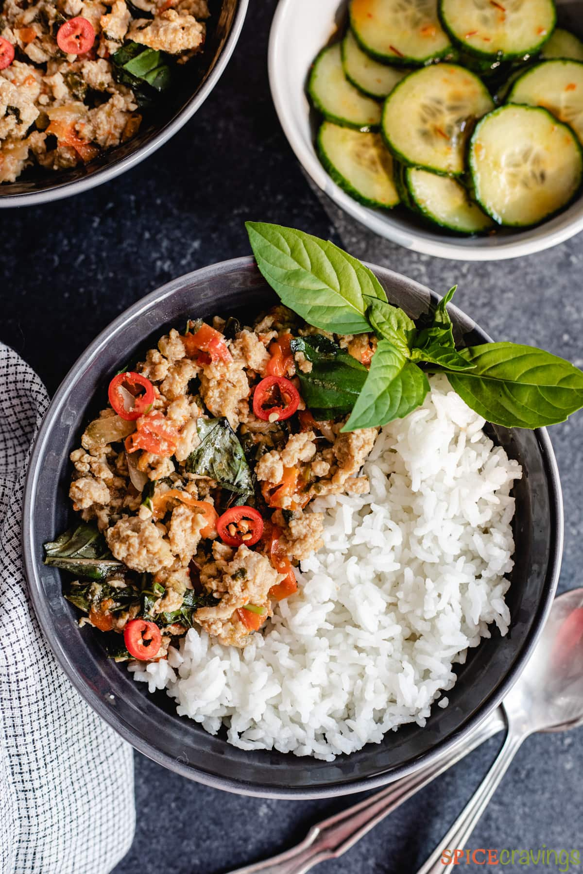 A bowl of chicken and vegetables topped with fresh basil and served with rice