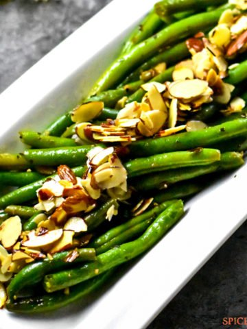 Green beans with almonds served on a white plate