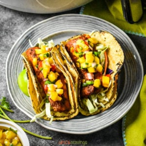Two grilled fish tacos topped with mango salsa