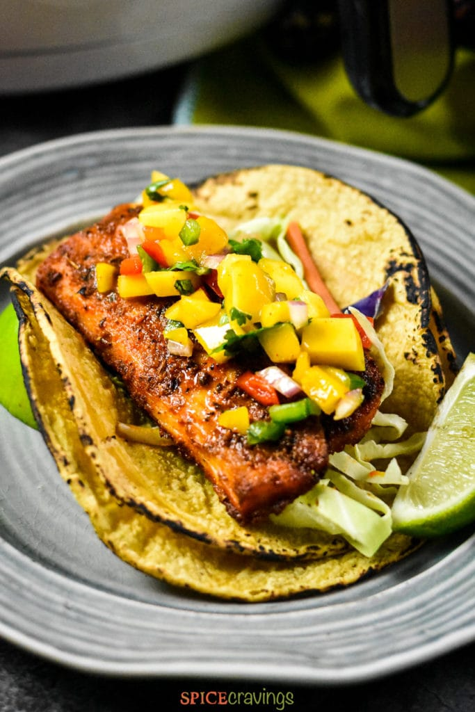 Spicy grilled fish on corn tortilla topped with mango salsa