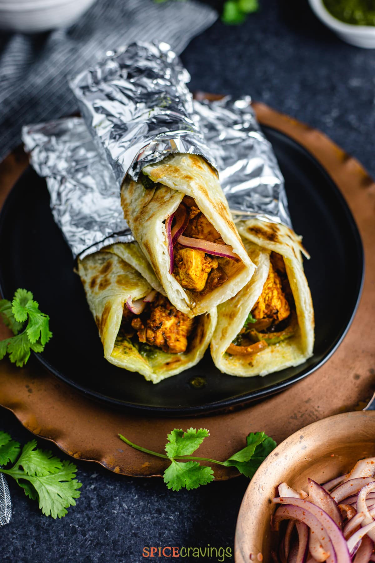 A stack of chicken kathi rolls on a plate
