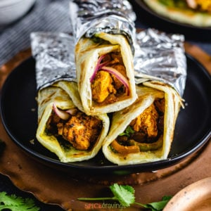 Chicken kathi rolls wrapped in aluminum foil on a plate