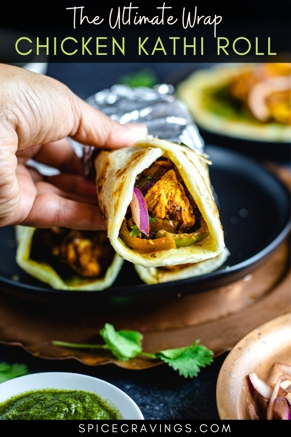 A hand holding a chicken kathi roll
