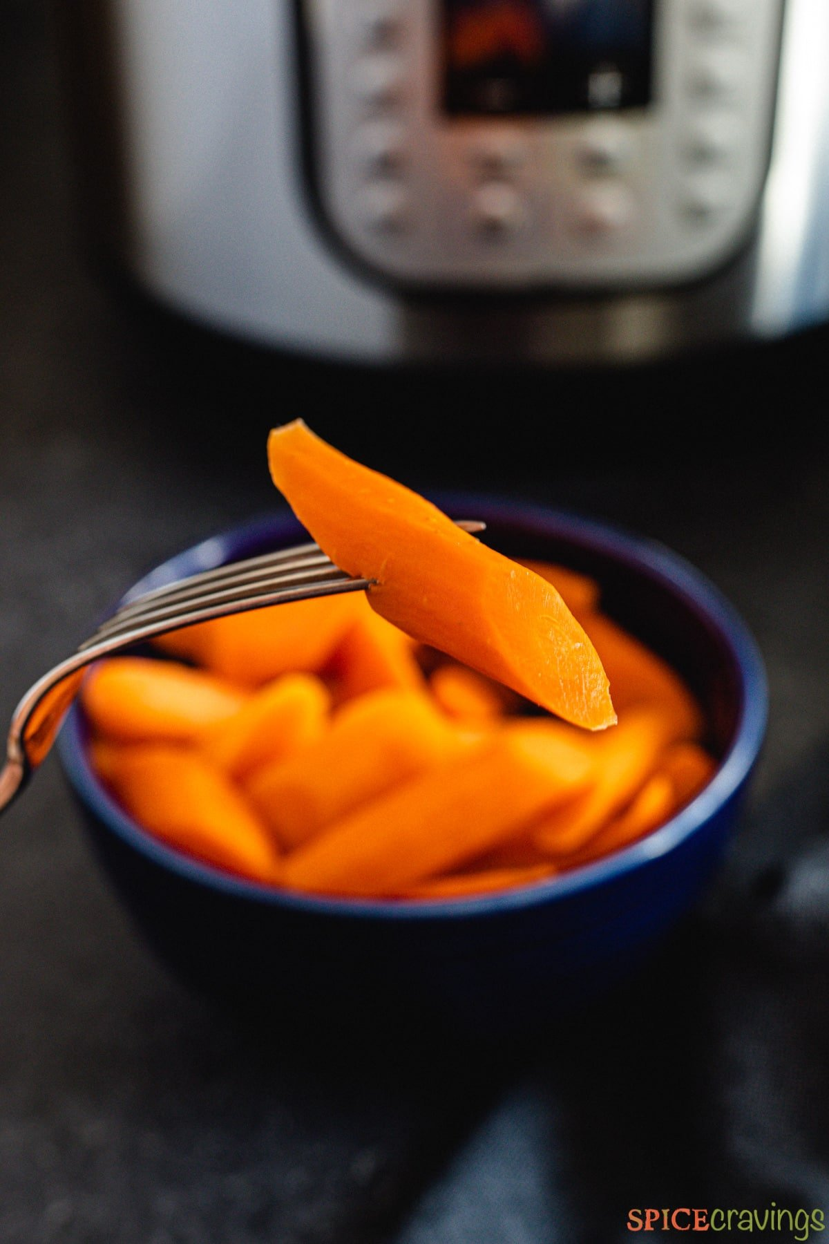 A fork lifting a steamed carrot from a bowl