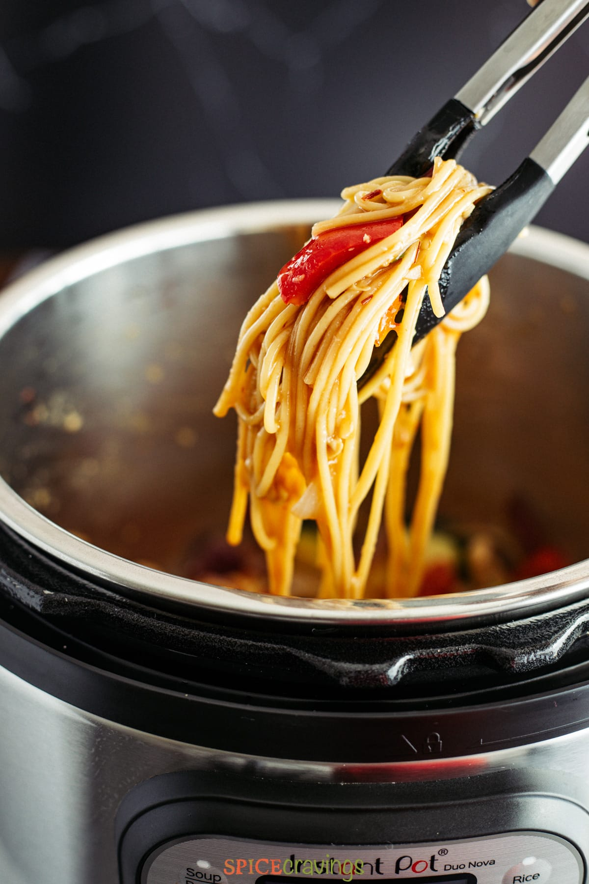 Noodles being lifted with tongs from an Instant Pot