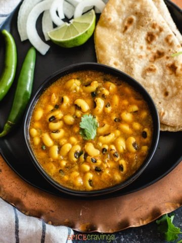 Black eyed peas curry in a black bowl with roti