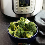A bowl of steamed broccoli in front of an Instant Pot