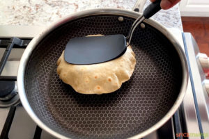 Gently pressing Indian roti with a spatula