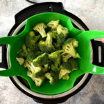 Broccoli in a steamer basket being lowered into a pressure cooker