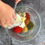 Mixing spices and yogurt in a bowl