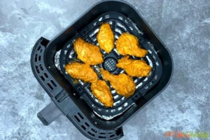 Chicken wings inside of an air fryer basket