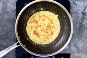 A paratha frying in a pan