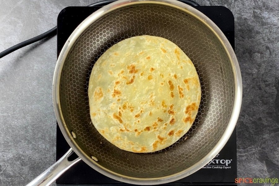 Paratha cooking inside a frying pan