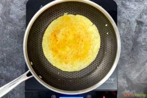 Paratha with egg mixture on top in a pan