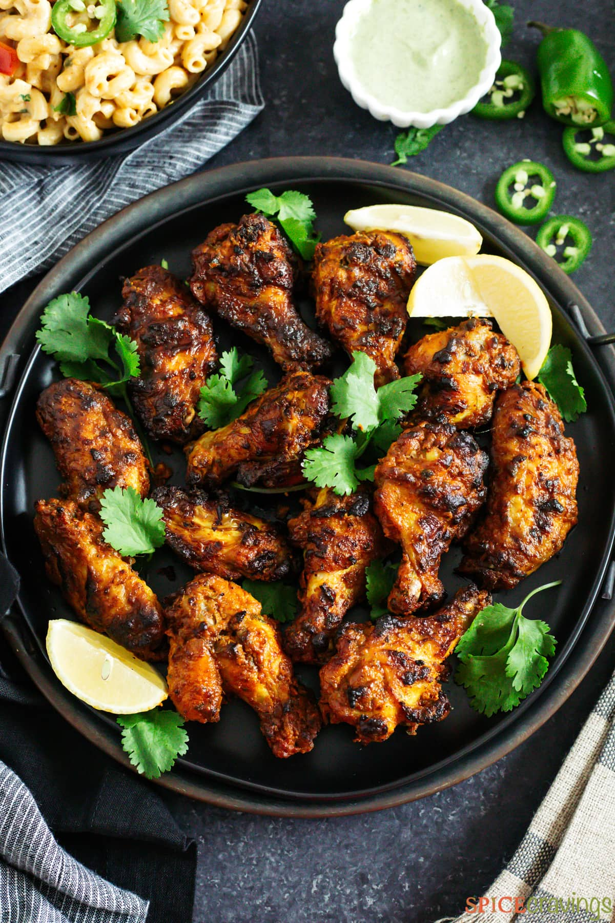 Tandoori chicken wings on a plate with wedges of lemon and cilantro
