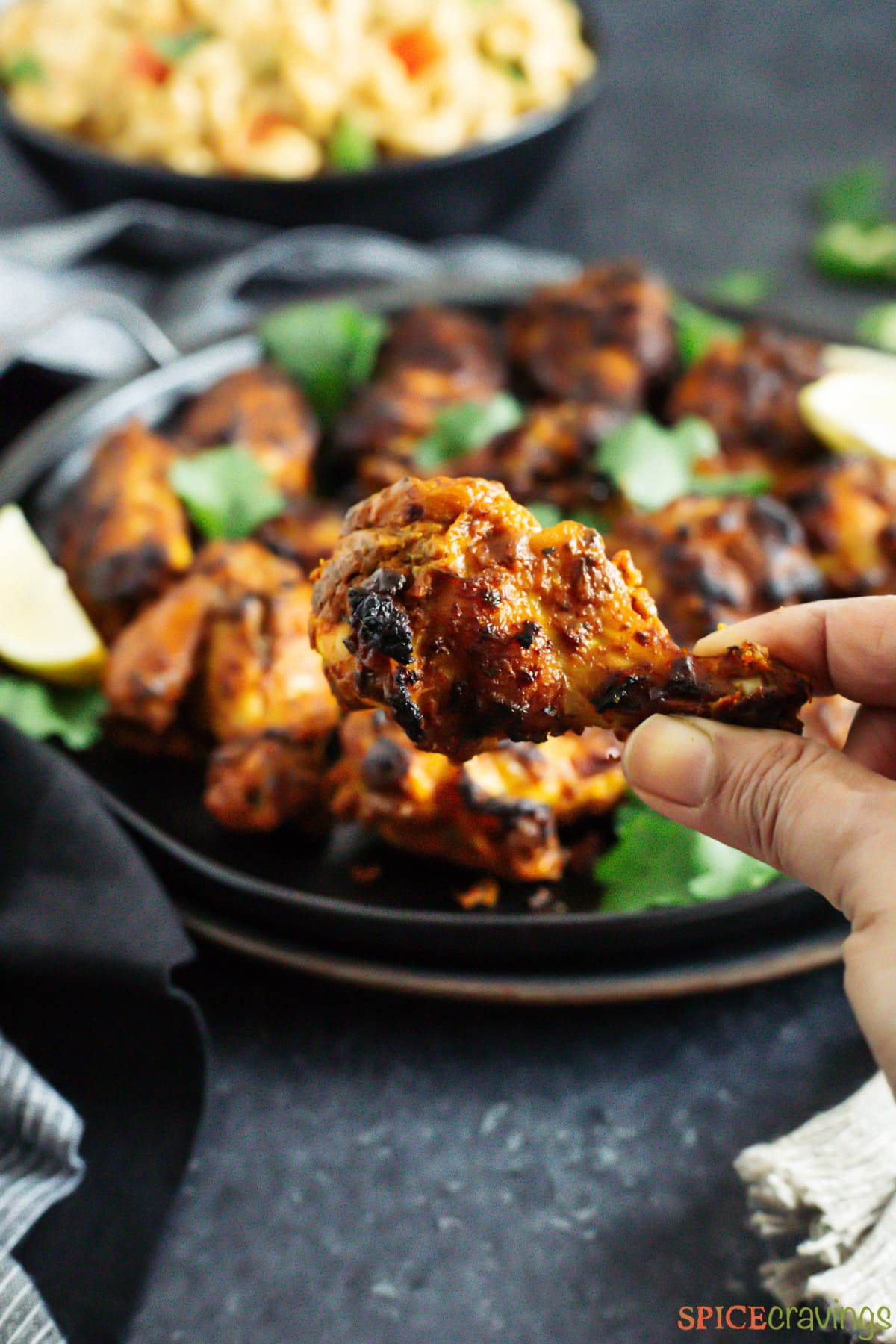 A hand lifting a tandoori chicken wing from a tray