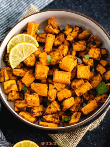 Cubes of roasted air fryer sweet potatoes in a bowl with lemon wedges