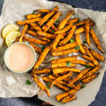 Air fried sweet potato fries on a plate with parchment paper