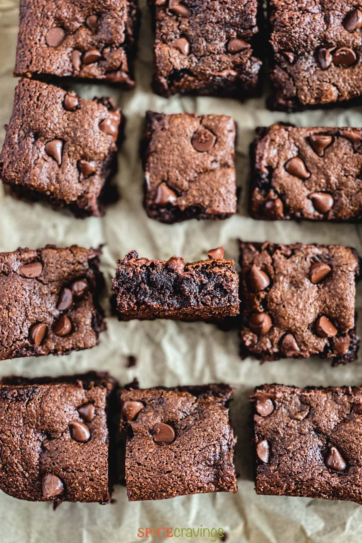 Gooey brownies on a piece of parchment paper