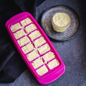 Pink ice cube tray and small jar filled with ground ginger and garlic