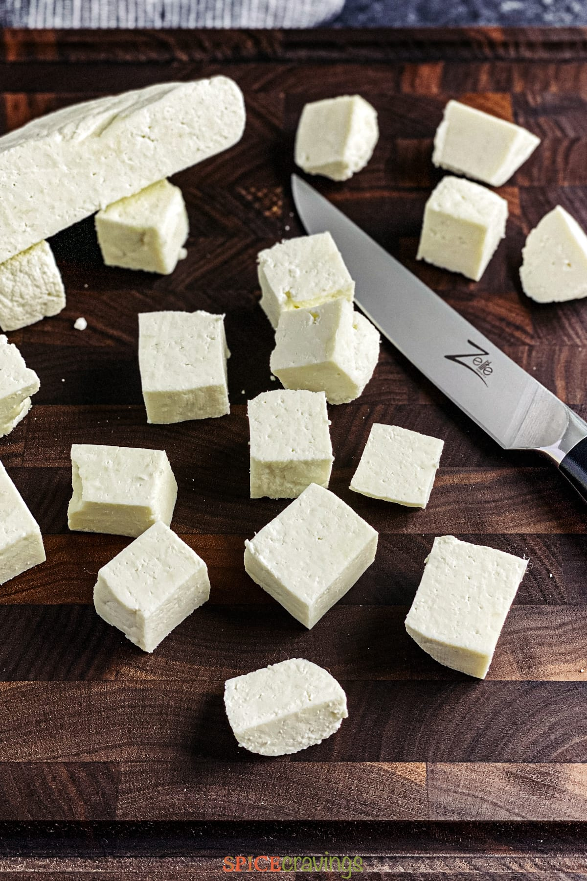 Chopped paneer on a cutting board next to a knife