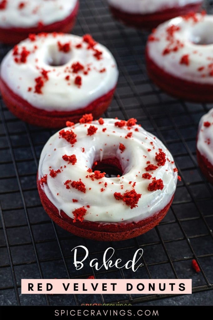 Glazed red velvet doughnuts on a wire rack