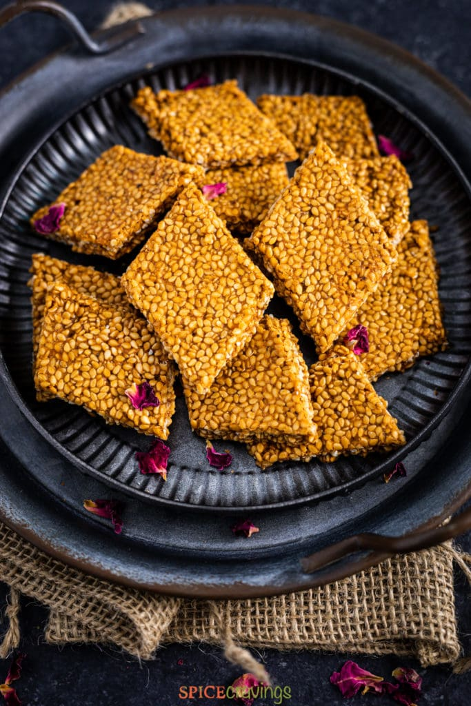 sesame chikki pieces on a metal plate