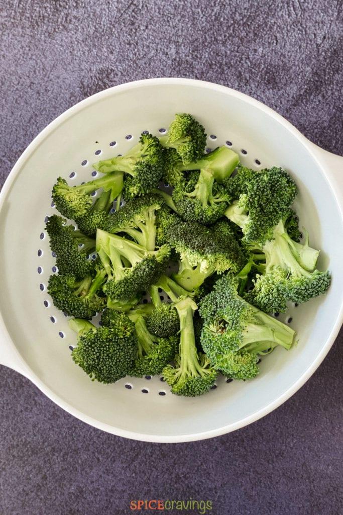 Broccoli florets in a white strainer