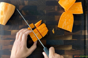 Cutting sweet potato on a cutting board with a knife