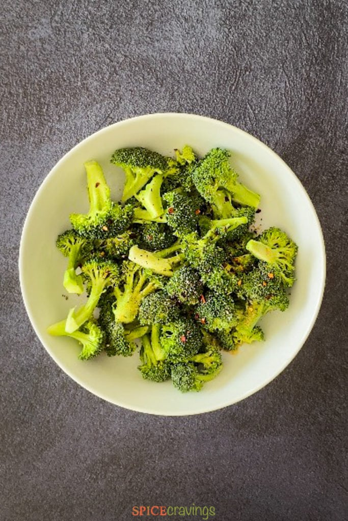 Broccoli florets with seasoning in a white bowl
