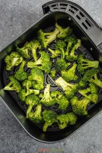 Green broccoli florets in air fryer basket